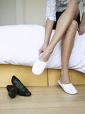 Woman Putting On Slippers In Bedroom Stock Image