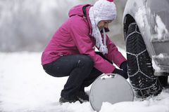 Woman putting snow chains. On to tyre of car Stock Image