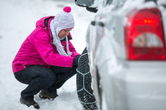 Woman putting snow chains. Winter, woman putting snow chains onto tyre of car Royalty Free Stock Images