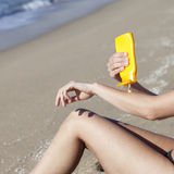 Woman putting some lotion on Stock Images