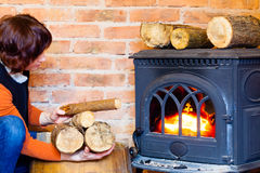 Woman putting some more wood on fireplace. Heating. Stock Images