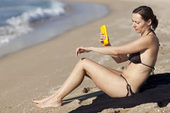Woman putting some sunblock on the beach Stock Photo
