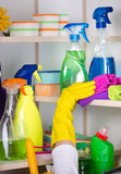 Woman putting spray bottle in pantry. Woman with safety gloves storing cleaners in pantry on the wall royalty free stock photo
