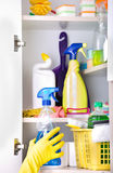 Woman putting spray bottle in pantry. Woman with safety gloves storing cleaners in pantry on the wall royalty free stock images