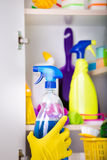 Woman putting spray bottle in pantry. Woman with safety gloves storing cleaners in pantry on the wall stock photo