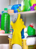 Woman putting spray bottle in pantry. Woman with safety gloves storing cleaners in pantry on the wall royalty free stock photography
