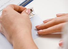 Woman putting on stamp envelop for bills Royalty Free Stock Photos