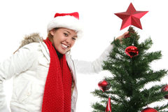 Woman putting star on tree Royalty Free Stock Image