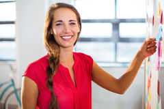 Woman putting sticky notes on whiteboard Royalty Free Stock Images