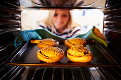 Woman Putting Stuffed Mushrooms Into Oven To Cook royalty free stock images