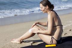 Woman putting suncream on her body Royalty Free Stock Photography