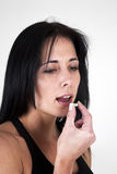 Woman putting tablet in her mouth. Woman putting headahce tablet in her mouth Royalty Free Stock Photos