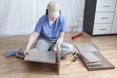 Woman putting together self assembly furniture assemble flat-pac Royalty  Free Stock Image