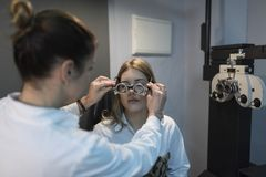 Trial frame test in optometry store. Woman putting on trial frame to ther in optometry shop royalty free stock photo