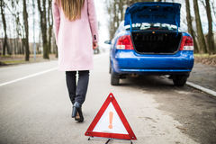 Woman putting a triangle on a road and back to brocken car. Woman putting a triangle on a road,car trouble Royalty Free Stock Image
