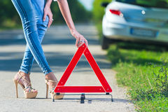 Woman putting a triangle on a road. Car trouble Stock Images