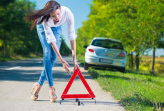 Woman putting a triangle on a road. Car trouble Royalty Free Stock Photography