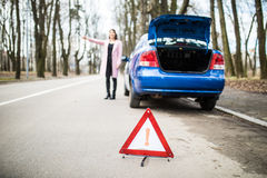 Woman putting a triangle on a road, car trouble trying to stop and get help from other driver from road. Woman putting a triangle on a road,car trouble Royalty Free Stock Images