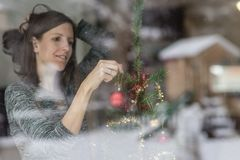 Woman putting up Christmas decorations at home Stock Image