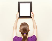 Woman putting up frame Stock Photo