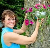 Woman putting up a hanging plant. Woman hanging a hanging plant outdoors royalty free stock photo