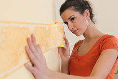 Woman putting up  wallpaper border Stock Photos
