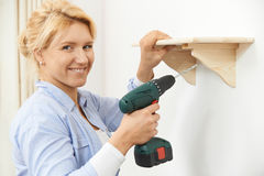 Woman Putting Up Wooden Shelf At Home Using Cordless Drill Royalty Free Stock Images