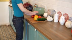Woman putting vegetables on the cutting board stock video