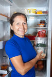 Woman putting   vegetables  into refrigerator Stock Images