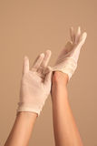 Woman putting on vintage white gloves Stock Image