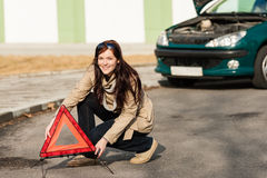 Woman putting warning triangle on the road Royalty Free Stock Image
