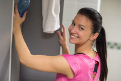 Woman putting water bottle in locker Royalty Free Stock Images