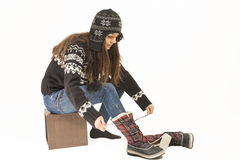 Woman putting on winter shoes. Royalty Free Stock Photo
