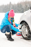 Woman putting winter tire chains car wheel. Woman putting winter tire chains on car wheel snow breakdown Stock Photo