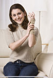 Woman Putting on Wrist Brace. A woman is seated on a living room sofa and putting on her wrist brace.  She is smiling at the camera.  Vertically framed shot Stock Photos