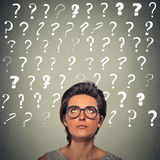 Woman with puzzled face expression and question marks above her head Royalty Free Stock Photos