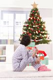 Woman in pyjama on christmas morning. Woman in pyjama having coffee on christmas morning, looking at tree Royalty Free Stock Photos