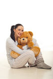 Woman in pyjama hugging bear Royalty Free Stock Photo