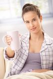 Woman in pyjama offering coffee Stock Images