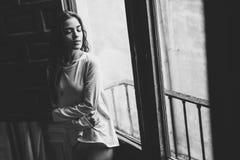 Woman in pyjama and white panties posing near a window Royalty Free Stock Photo
