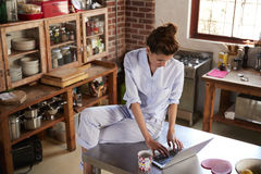 Woman in pyjamas sits using laptop in kitchen, high angle Stock Images