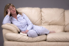 Woman in pyjamas sleeping on a sofa Royalty Free Stock Images