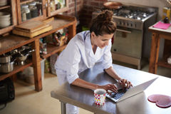 Woman in pyjamas stands using laptop in kitchen, high angle Royalty Free Stock Photo