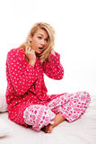 Woman in pyjamas yawning. Attractive young blonde woman sitting cross legged on her bed in pyjamas yawning as she tries to wake up Royalty Free Stock Images