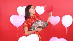 Woman in Qipao chinese dress. With fan and red heart shape and balloon isolated on red background stock video