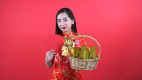Woman in Qipao chinese dress. Holding golden bar in gift basket isolated on red background stock video