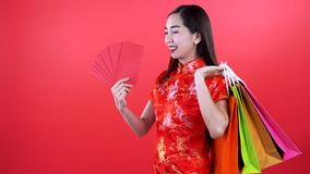 Woman in Qipao chinese dress. Holding money and golden bar in gift basket isolated on red background stock video