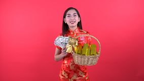 Woman in Qipao chinese dress. Holding money and golden bar in gift basket isolated on red background stock footage