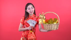 Woman in Qipao chinese dress. Holding money and golden bar in gift basket isolated on red background stock video footage