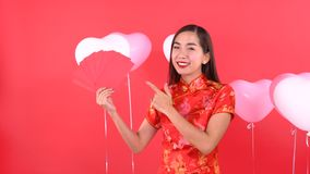 Woman in Qipao chinese dress. Holding red pocket momey isolated on red background stock video